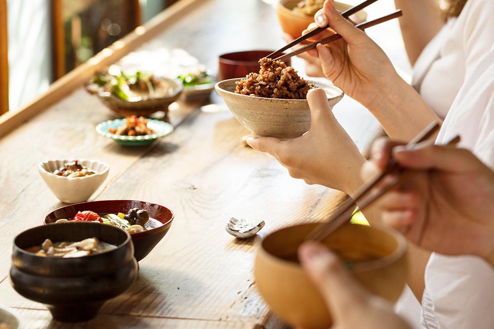 玄米ごはんのある食卓でごはんを食べる人たちのイメージ
