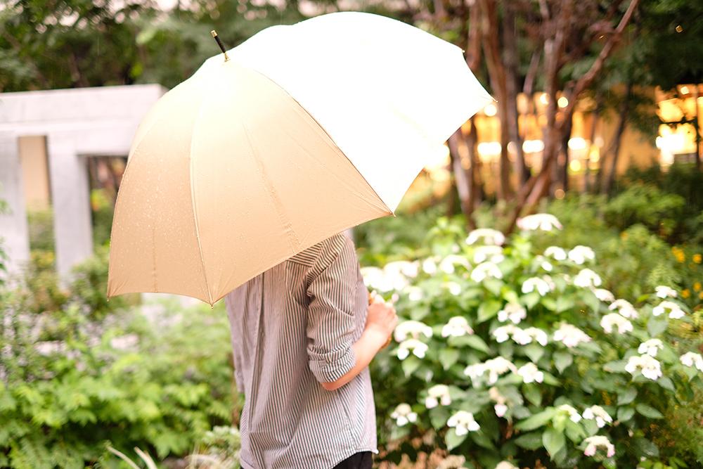 傘をさして立つ女性の後ろ姿