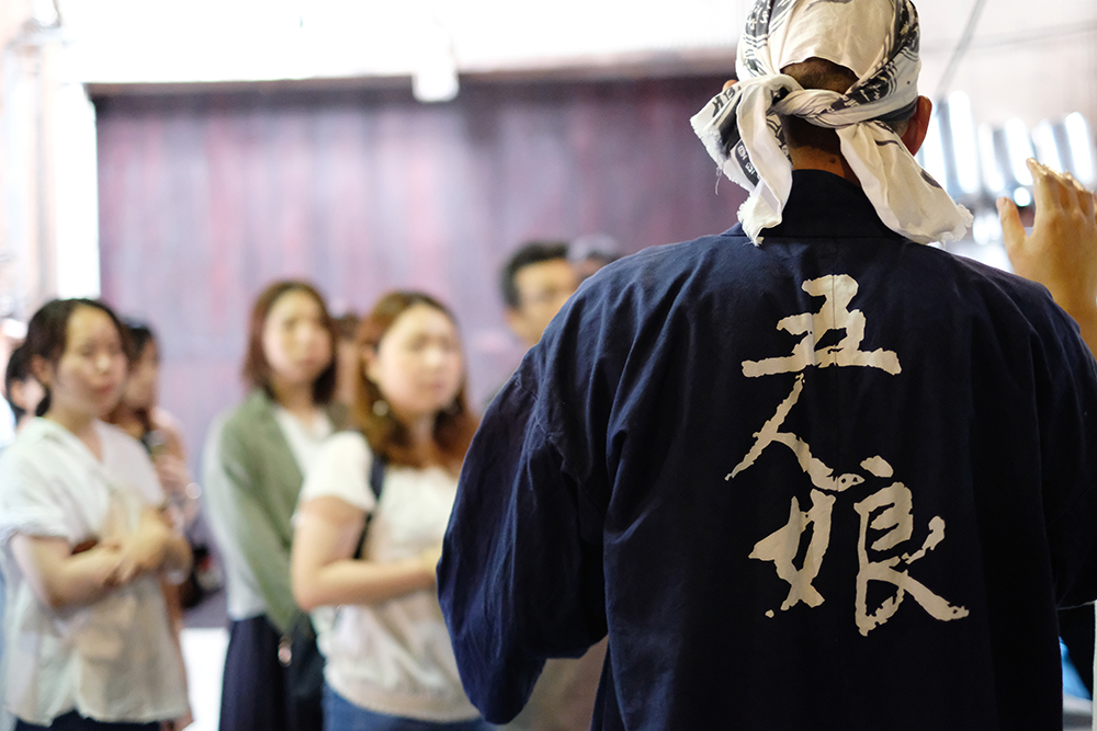 日本酒「五人娘」のロゴ入り法被を着た杜氏の後ろ姿